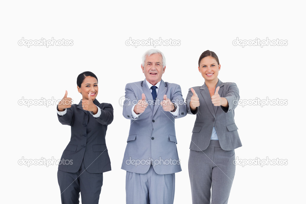 Three businesspeople giving thumbs up against a white background — Stockfoto #10321918