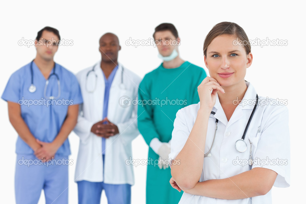 Thoughtful doctor with male colleagues behind her against a white background — Photo #10322700