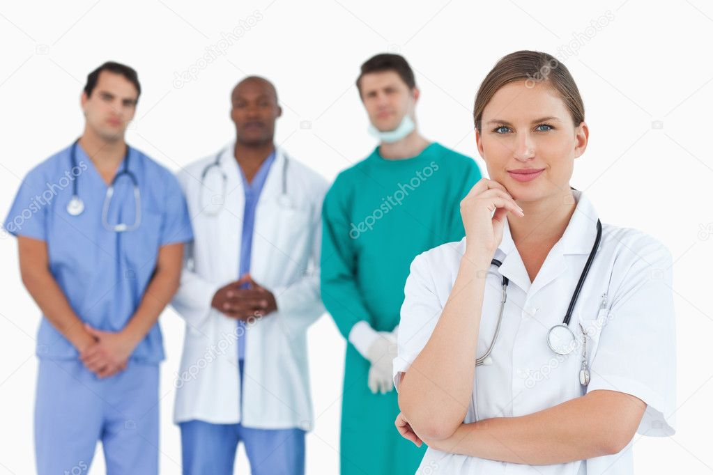 Thoughtful doctor with male colleagues behind her against a white background  Foto de Stock   #10322700