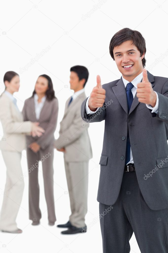 Salesman giving thumbs up with team behind him against a white background — Stock Photo #10323175