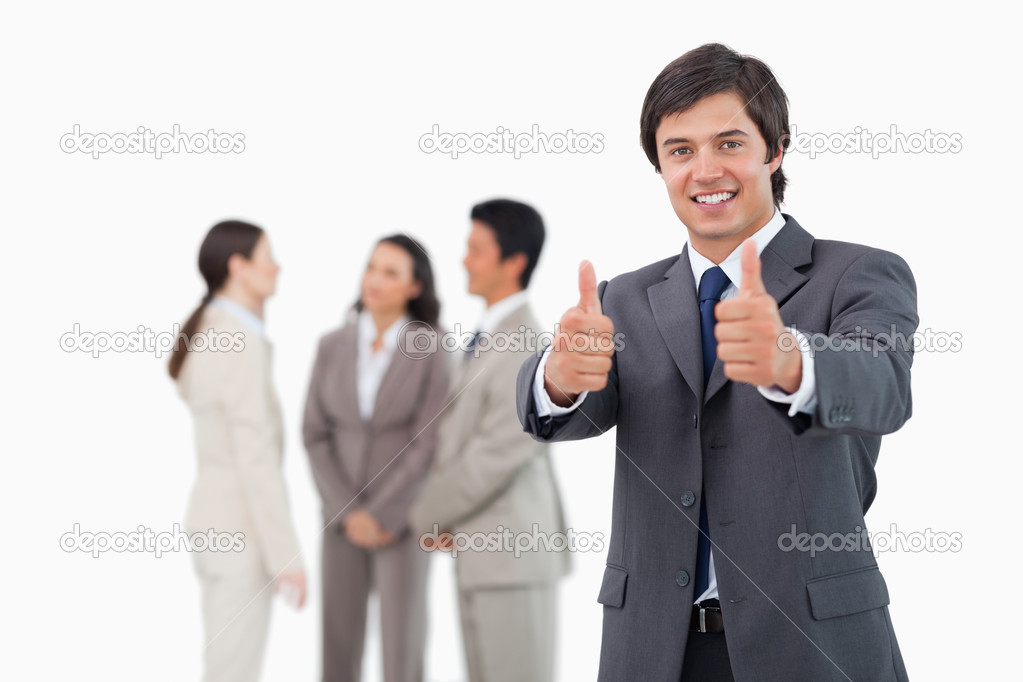 Salesman giving his approval with team behind him against a white background — Stock Photo #10323177