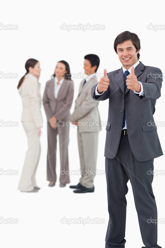 Salesman giving thumbs up with colleagues behind him against a white background  Stock Photo #10323179