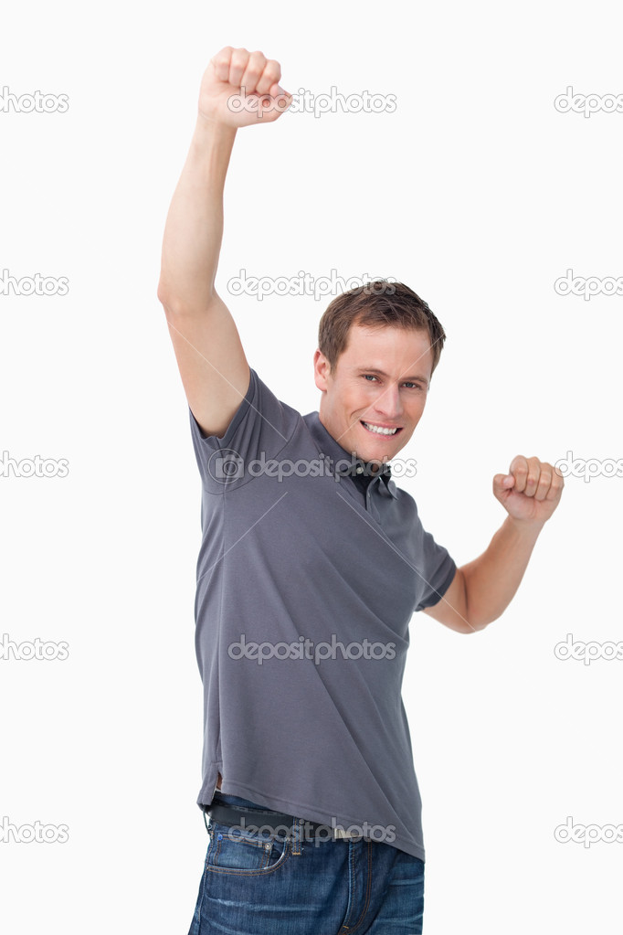 Victorious young man raising fist against a white background — Stock Photo #10323448