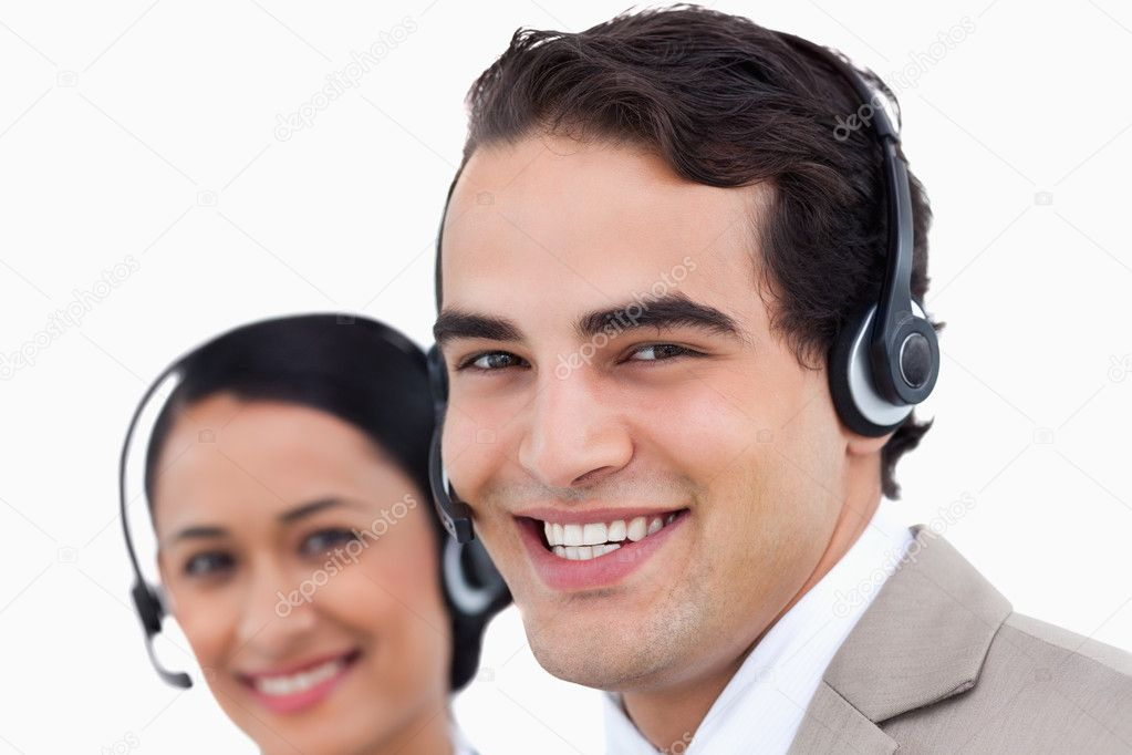 Close up side view of smiling call center agents at work against a white background — Stock Photo #10325776