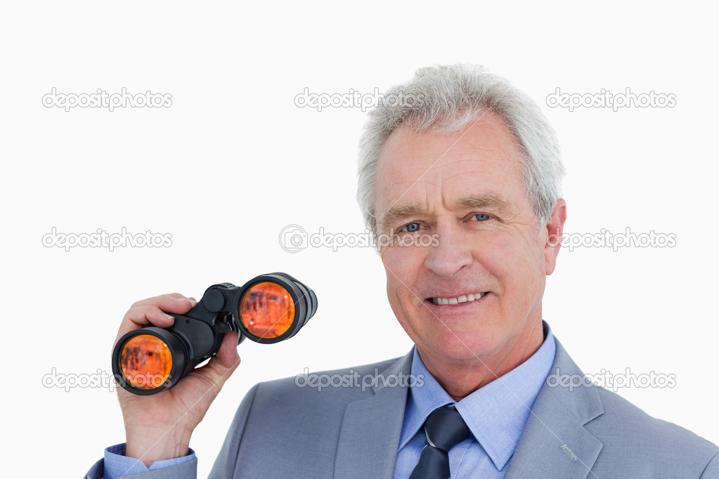 Close up of smiling mature tradesman with spy glass against a white background — Stock Photo #10326426