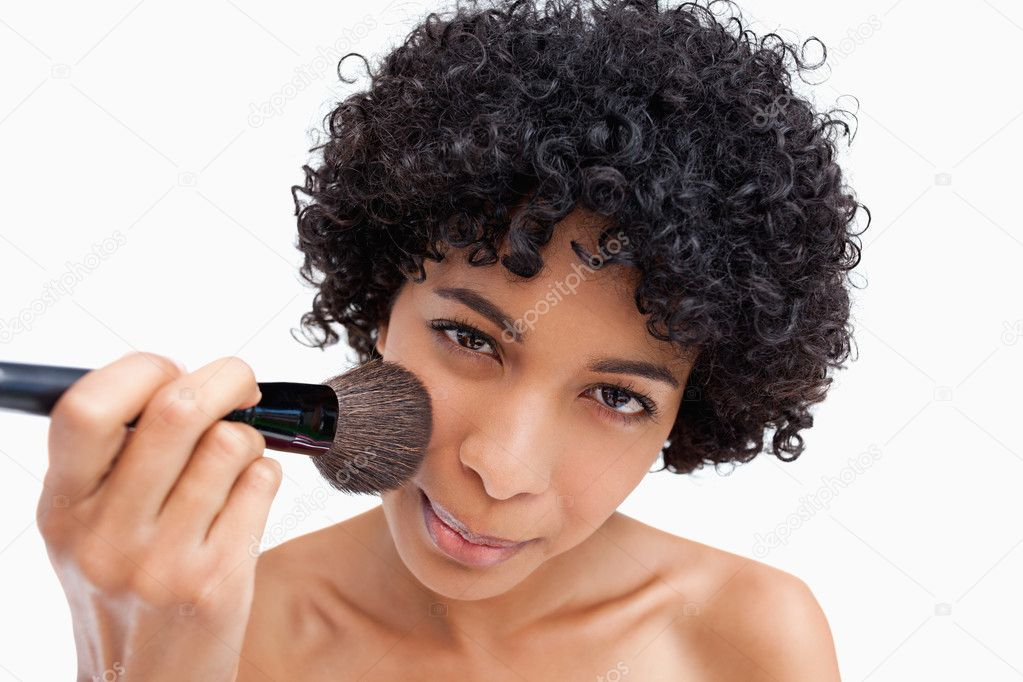Young woman applying natural blush on her face with her powder brush  Stock Photo #10327191