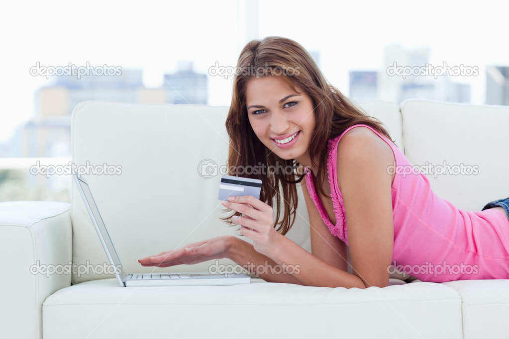 Young woman showing a beaming smile while holding a grey credit card — Stock Photo #10327287