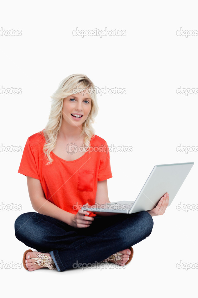 Attractive woman sitting cross-legged holding her laptop while being relaxed  Stock Photo #10327493
