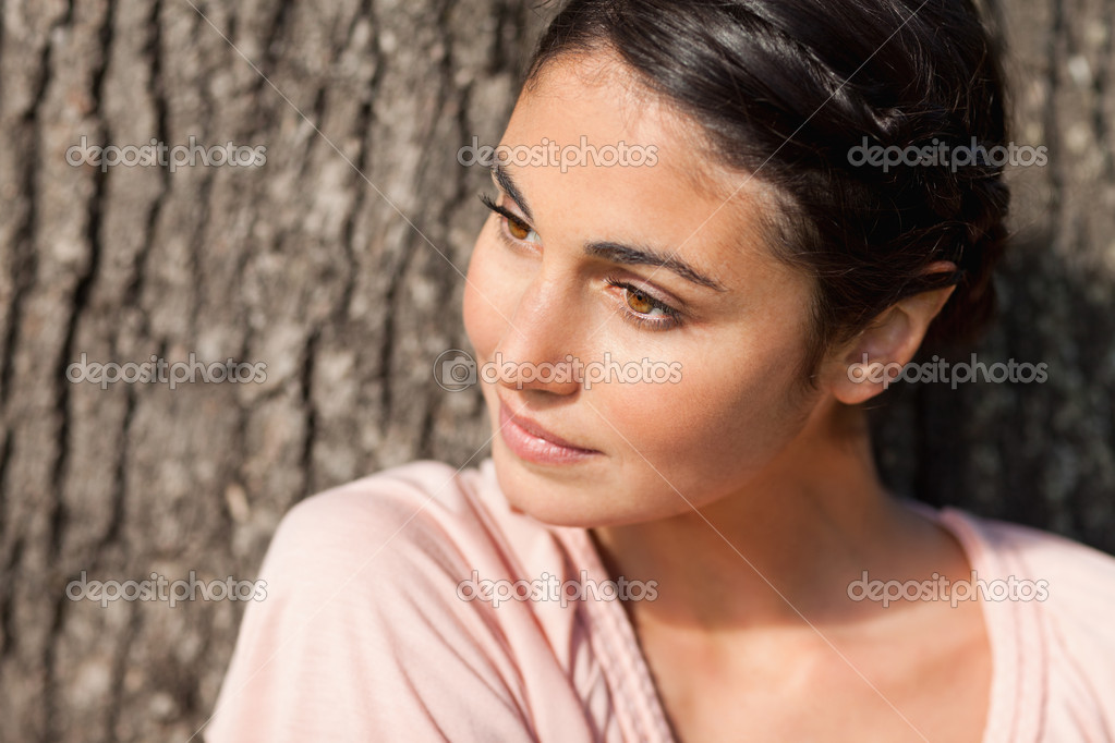 Woman sitting against a tree while looking towards her left as the sun is shining on her face  Stock Photo #10329746