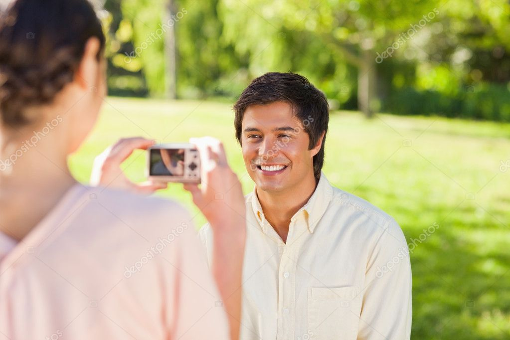 Using a camera, the woman takes a photo of her friend smiling in the park  Stock Photo #10329810