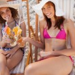Young women in beachwear clinking their cocktails while looking — Stock Photo
