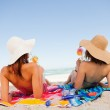 Back view of beautiful women sunbathing while sipping cocktails — Stock Photo