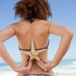 Young woman in swimsuit holding a starfish on her back — Stock Photo