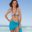 Smiling young woman wearing a blue sarong in front of the sea — Stock Photo