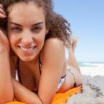 ung kvinna liggande samtidigt visar ett stort leende med sin handmladá žena vleže vykazovala velký úsměv s rukou — Stockfoto