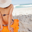 Rear view of a woman sunbathing while sitting on a beach towel — Stock Photo