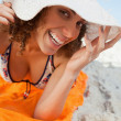 Young smiling woman holding her hat brim while lying down - Stock Photo