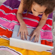 Young smiling woman lying on her beach towel while typing on her — Stock Photo