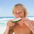 Young man eating a piece of watermelon in front of the sea — Stock Photo