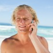 Blonde man talking on his mobile phone while standing on the bea — Stock Photo #10330487