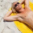 图库照片: Overhead view of a blonde man lying on his beach towel