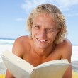 Smiling blonde man reading a book while lying on the beach — Stock Photo #10330533