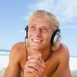 Smiling man looking up while listening to music with his headset — Stock Photo #10330535