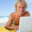 Smiling blonde man lying on the beach while using his laptop — Stock Photo