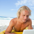 Blonde man lying on the beach while using his laptop in a very c — Stock Photo #10330545