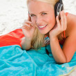Smiling young blonde woman looking at the camera while listening - Stock Photo
