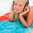 Young woman closing her eyes while listening to music on her bea — Stock Photo