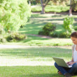 Woman sitting on the lawn working on her notebook — Stock Photo