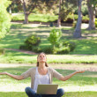 Woman sitting on the lawn in a yoga position with a laptop — Stock Photo #10330724