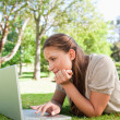 Woman lying on the lawn while using her laptop — Stock Photo #10330761