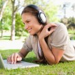 Woman with a laptop and a headset lying on the lawn — Stock Photo