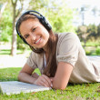 Smiling woman with a headset and a laptop lying on the lawn — Stock Photo