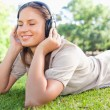 Woman enjoying music on the lawn — Stock Photo