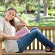 Side view of a smiling woman sitting on a park bench with her bo — Stock Photo #10330845