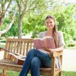Smiling woman with a book and a guitar sitting on a bench — Stock Photo #10330857