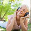Smiling woman with headphones enjoying music on the lawn — Stock Photo