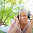 Smiling woman with headphones enjoying music on the grass - Stock Photo