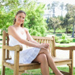 Smiling woman with her legs crossed sitting on a park bench — Stock Photo