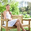 Woman with her legs crossed sitting on a park bench — Stock Photo