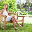 Woman with her legs crossed sitting on a bench — Stock Photo