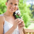 Smiling woman with a flower sitting on a bench — Stock Photo