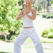 Smiling woman doing yoga exercises in the park — Foto Stock