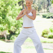 Smiling woman doing yoga exercises in the park — Stockfoto