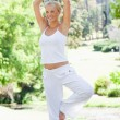 Smiling woman doing her yoga exercises in the park — Stock Photo #10331045