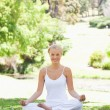 Smiling woman sitting in a yoga position in the park - Stok fotoğraf