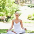 Woman sitting in a yoga position on the grass - Stock Photo